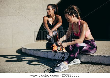 Fitness women resting after workout. Woman sitting outdoors after workout session with a female friend in background.