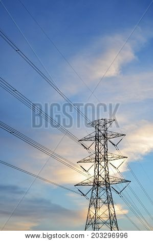 Silhouette of electricity post on blue sky background.High voltage power line.