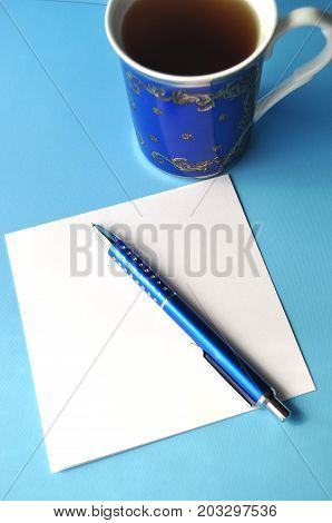 Blue porcelain china cup with blue pen and pencils, white note card and blue background