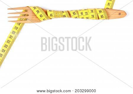 Wooden fork wrapped centimeter concept of slimming healthy lifestyle and nutrition copy space for text on white background