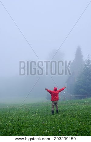 Rear view of man in fog with outstretched hands. Morning in Carpathian mountains