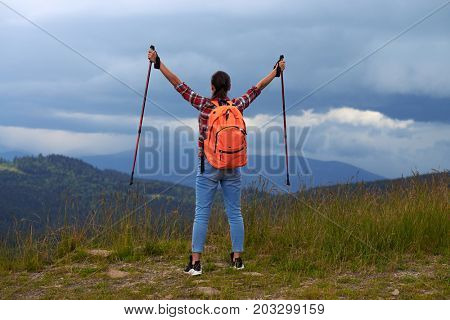 Rear view of young female with hiking poles outstretched hands. Female hiker with backpack