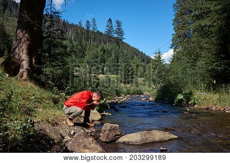 Mid shot of thirsty hiker drinking water in mountain river