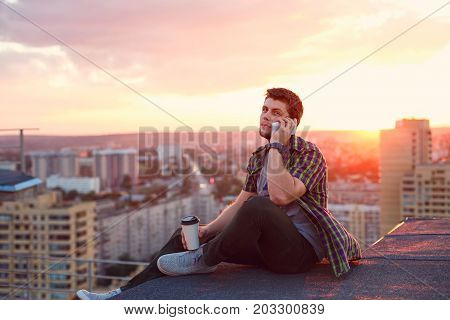 A hipster man drinks coffee and talks on his cell phone. He sits on the roof of a high-rise building at sunset. Portrait on a background of sunset and cityscape skyline