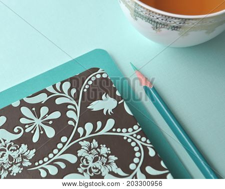 White fine china cup of tea with a blank note card and teal book on mint background