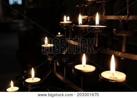 Beautiful votive prayer candles lit in a brass sconce holder in a church.