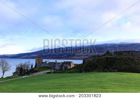 Panoramic view of Urquhart Castle and fortress with Scottish Flag waving on a winter's day with snow capped mountains and Loch Ness in the background.