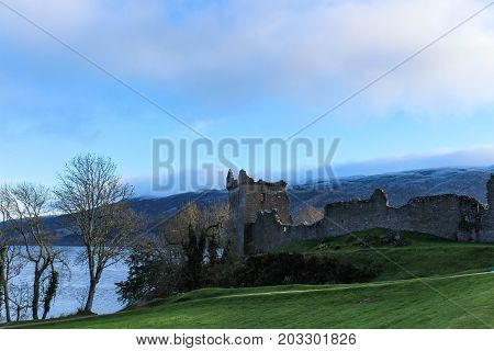 Snowy winter's view of Urquhart Castle with barren trees and Loch Ness in the background.