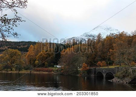 Gorgeous autumn scene of a snow capped mountain, Loch, colorful foliage and bridge in the early winter in the Scottish Highlands.