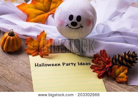 Halloween Party Ideas list concept on notebook and wooden board