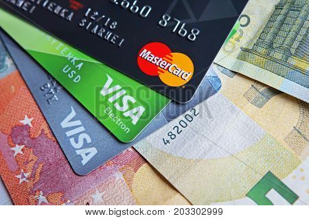 Berlin Germany - September 4 2017: Money concept. MasterCard and Visa bank cards laying on euro banknotes macro