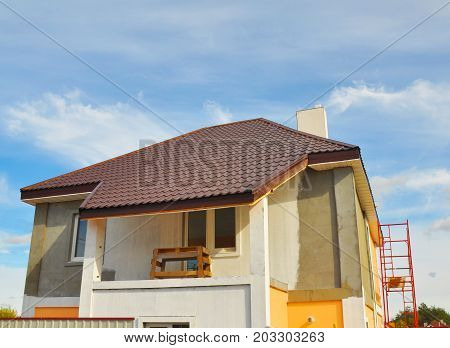 Construction or Repair of the Rural House with Balcony Eaves Windows Chimney Roofing Fixing Facade Insulation Plastering and Painting Walls. Painting House Facade Wall. Bad Roofing.