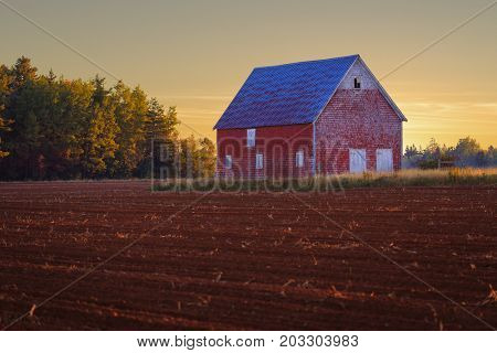 Red barn overlooks a plowed potato field.
