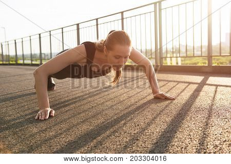 A woman in sportswear doing push ups in the city park in sunny evening.