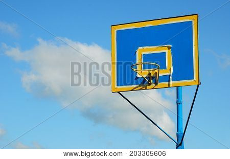 Just painted new colorful backboard and basketball hoop against blue cloudy sky.