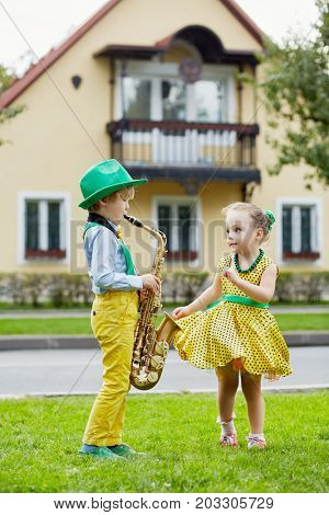 Little boy in dancing suit plays saxophone and little girl dances on grassy lawn against two-storied house.