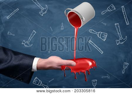 A businessman's hand turned palm up receives a handful of red paint flowing from a small overturned bucket. Repair works. Become a contractor. Home renovation business.