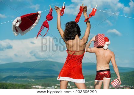 Couple in love of man and girl hanging clothes for drying. New year guy with muscular body on blue sky. Laundry and dry cleaning. Xmas red costume on rope with pin. Christmas man and woman family.
