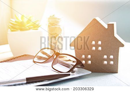 Business, finance, saving money, property ladder or mortgage loan concept : Wood house model, coins and financial statement or saving account book on desk table