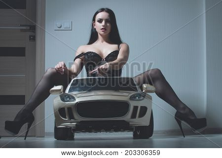 Girl in car toy. Driver girl sit in car. Beauty and fashion. escort and sexual services. Woman in black lingerie and shoes.