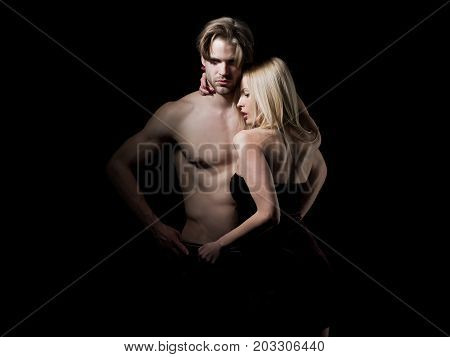Boyfriend and girlfriend on black. Relations of girl and guy. Love and romance. Man with muscular body with sexy girl. Couple in love of sexy man and woman.