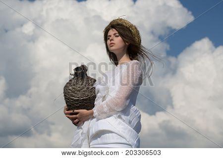 Girl With Wicker Wine Bottle On Cloudy Sky