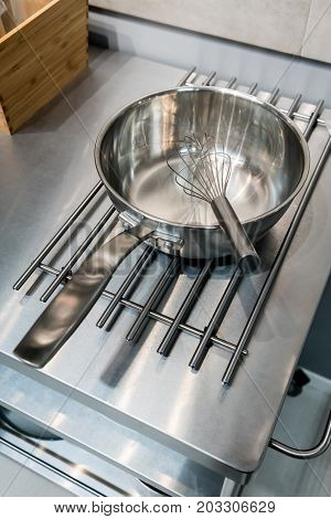 Silver metal whisker in stainless steel frying pan from high angle with reflection on pot coaster.