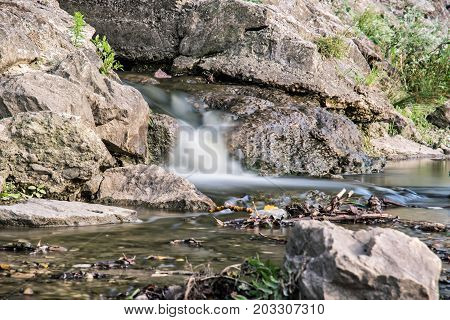 Water stream. Long time photo exposure. Detailed natural photo. Brook scene.