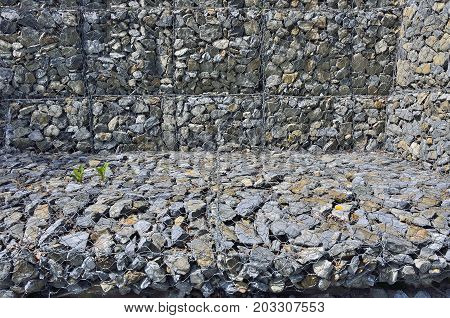 Gabion - stones in wire mesh. Popular element of design for garden landscaping and erosion control.