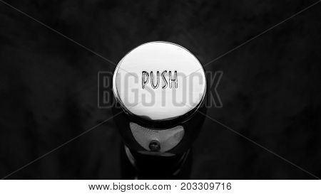 Close up flushing button of sanitary ware over black background.