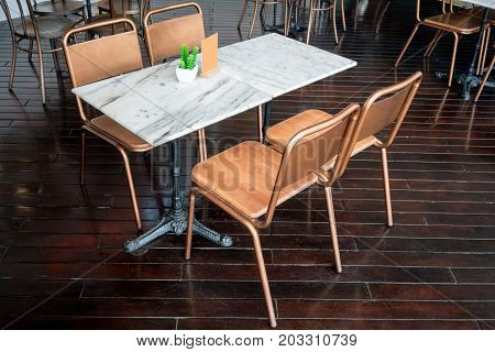 Dining marble table with brass metal chairs for dining out on dark wooden floor.