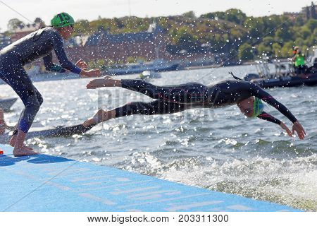 STOCKHOLM - AUG 26 2017: Two female swimmer wearing black swimsuit jump into the water in the Women's ITU World Triathlon series event August 22 2017 in Stockholm Sweden
