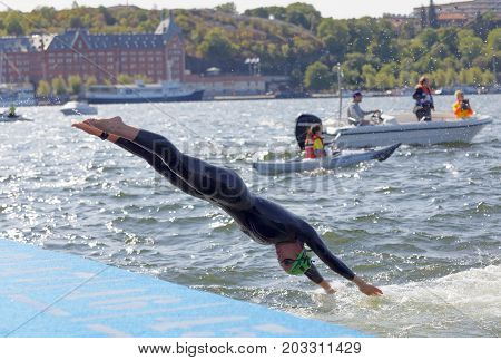 STOCKHOLM - AUG 26 2017: Female swimmer wearing black swimsuit jump into the water in the Women's ITU World Triathlon series event August 22 2017 in Stockholm Sweden