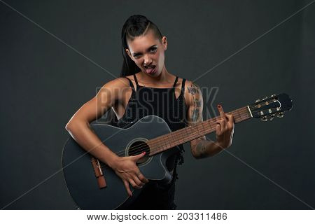 Rebellious woman showing middle finger when playing guitar