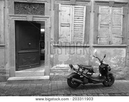 MALCESINE, ITALY - August 8: Scooter in front of an old house with morbid charm. ITALY 2014.