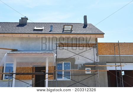Construction or repair of the rural house with skylights ventilation eaves windows garage doorway chimney roofing fixing facade insulation plastering and using color.