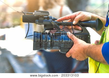Camera in the hands of a journalist cameraman. poster