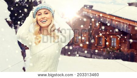 winter, vacation, christmas and people concept - smiling young woman in hat, sweater and gloves over wooden country house and snowflakes background
