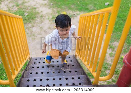 Asian Kid Goes Up The Stairs In The Park. Concept Of Growing Up.