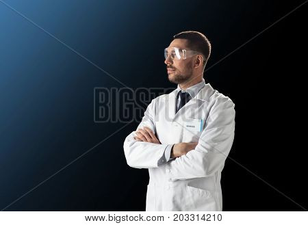 science, technology and people concept - male doctor or scientist in white lab coat and safety glasses over black background