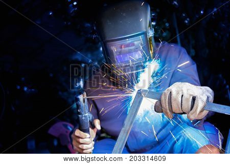 Welder wear protective mask welding metal structure with light sparkle
