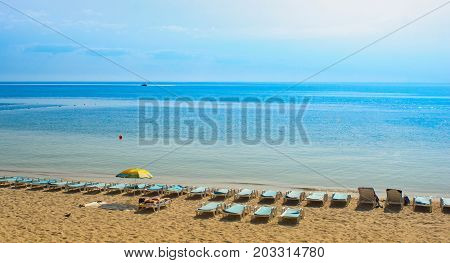 Seascape. Quiet still sunny beach, clear and transparent sea water, bright blue sky and white clouds at the distant horizon beauty