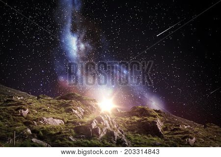 nature and astronomy concept - rocky landscape over night sky or space with shooting stars background