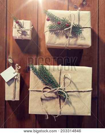 christmas, holidays, presents, new year and decor concept - close up of gift boxes wrapped into brown mail paper and decorated with fir brunch and rope bow