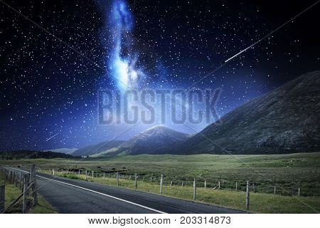 travel, astronomy and landscape concept - landscape with asphalt road and mountains over night sky or space with shooting stars background