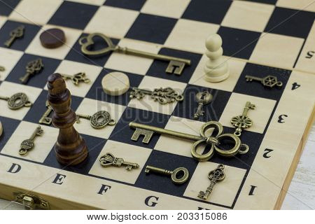 Ancient vintage keys on a classic chessboard