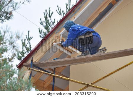 Roofer on the Corner of House Install Soffit. Roofing Construction. Soffit is Usually Constructed of Vinyl Wood or Aluminum and is Installed on the Underside of Roof Overhangs and Eaves.
