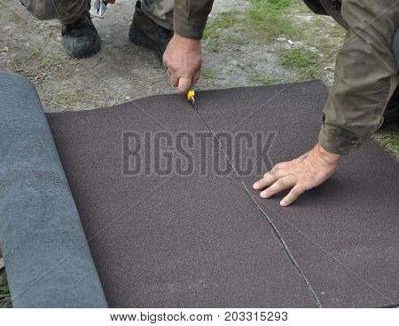 Construction worker cutting roll roofing felt or bitumen during waterproofing works.