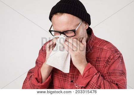 Caucasian Man with handkerchief sneezing feeling unwell. Be ill with influenza