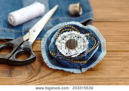 Blue denim flower brooch or hair accessory. Scissors, thread, thimble, needle, old jeans on a wooden table. Recycled denim fabric. Creative uses old jeans. Cheap home craft idea. Closeup poster